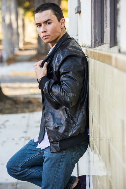 Serious Mixed Race man leaning on wall wearing leather jacket