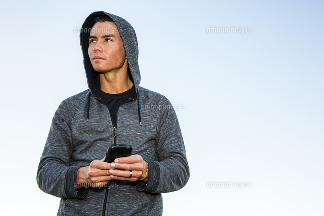 Mixed Race man wearing hoody texting on cell phone