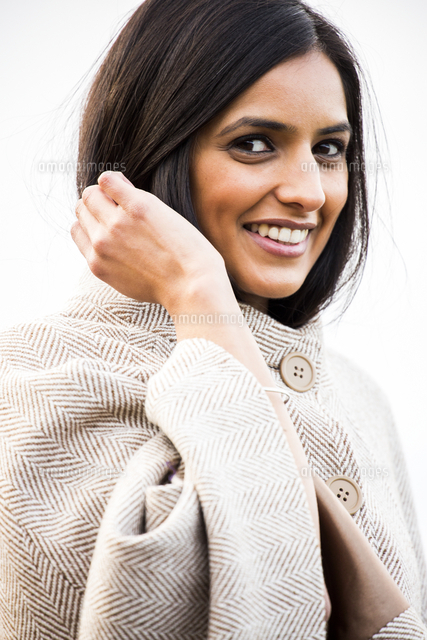 Portrait of smiling Indian woman wearing coat