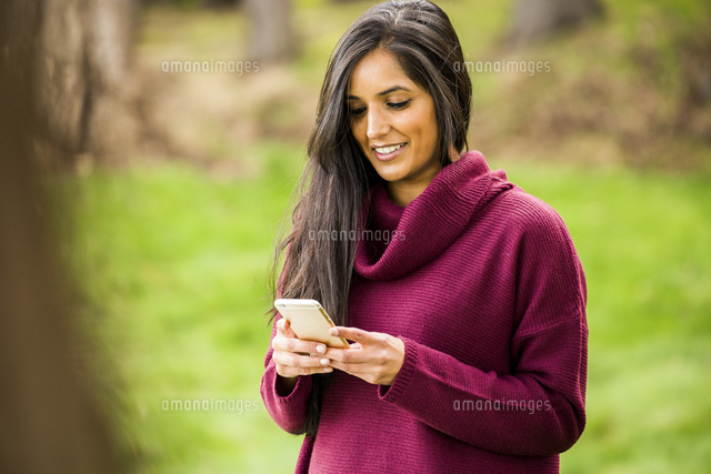 Smiling Indian woman texting on cell phone