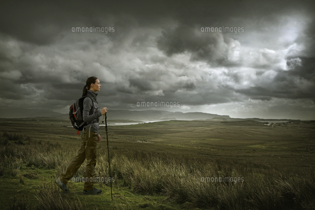 Caucasian woman hiking in green landscape