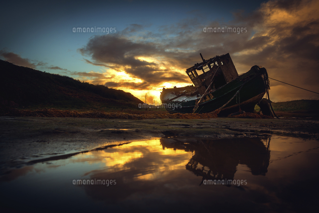 Shipwreck on beach at sunset