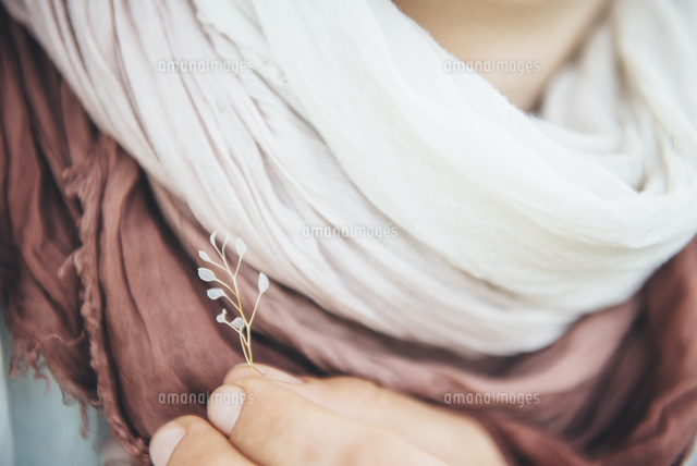 Caucasian woman holding delicate leaf near scarf