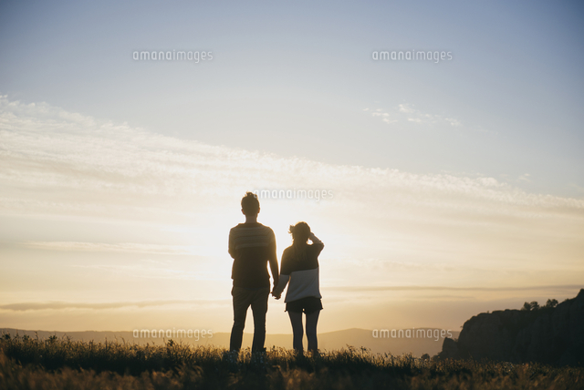 Caucasian couple admiring scenic view at sunset