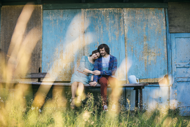 Caucasian couple holding hands sitting on table outdoors
