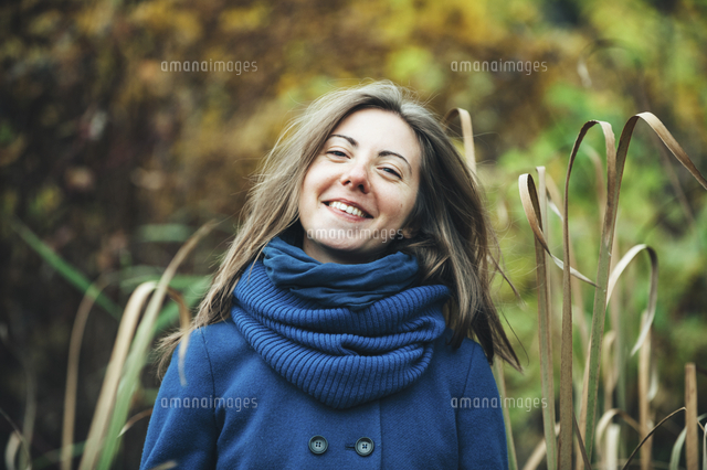 Smiling Caucasian woman wearing blue coat and scarf