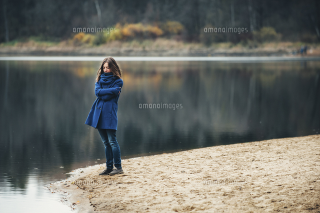 Caucasian woman wearing blue coat and scarf near lake