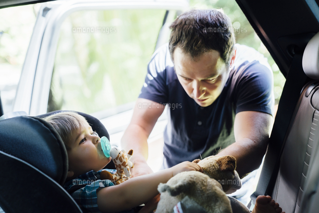 Father buckling son into car seat