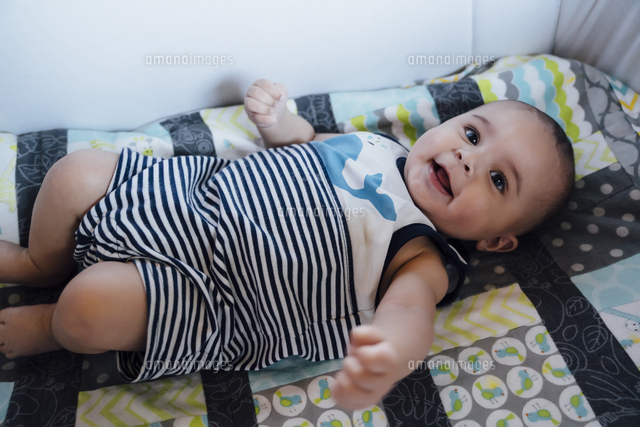 Smiling Mixed Race baby boy laying in crib