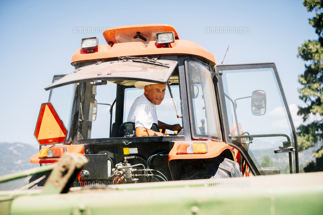 Caucasian farmer driving tractor