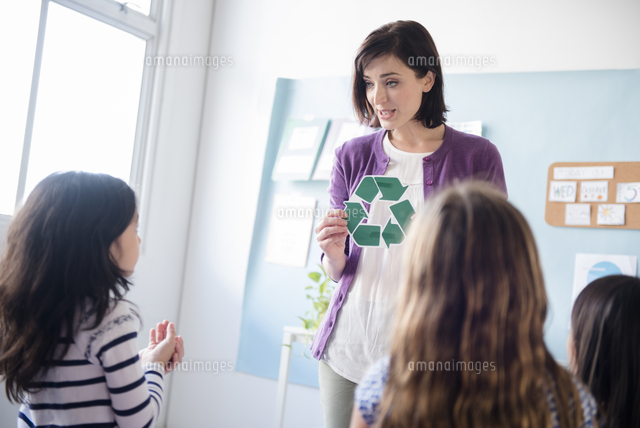 Teacher showing recycling symbol to girls in classroom