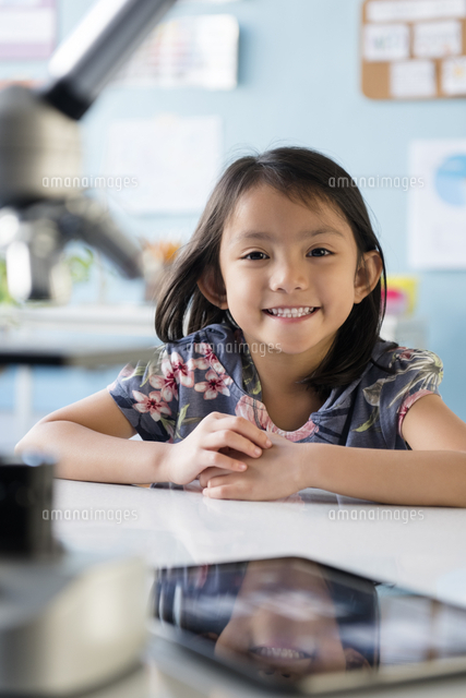 Smiling Asian girl leaning posing at desk