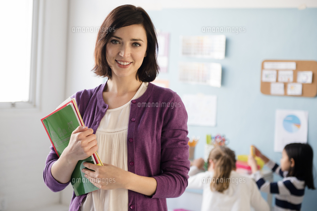 Portrait of smiling teacher holding notebooks in classroom