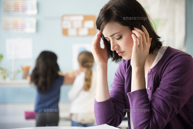 Caucasian teacher with headache in classroom