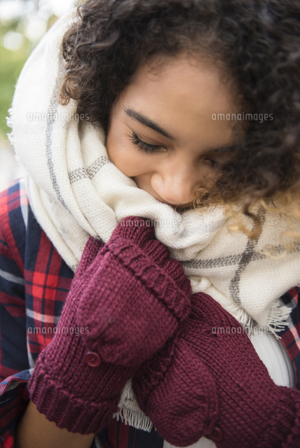 Mixed Race woman covering face with scarf