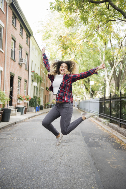 Mixed Race woman jumping for joy in city