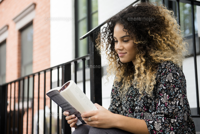 Mixed Race woman reading book in city