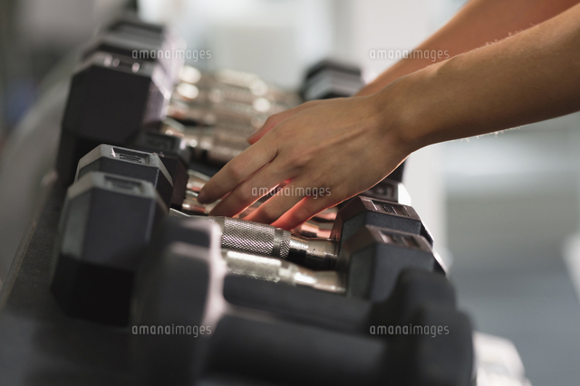 Hands of Mixed Race woman reaching for dumbbells