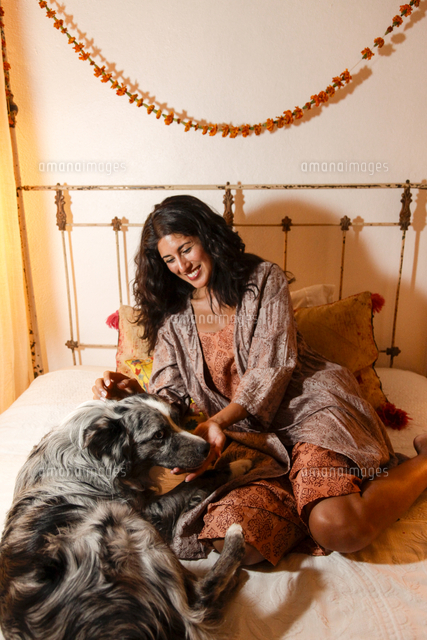 Hispanic woman sitting on bed petting dog