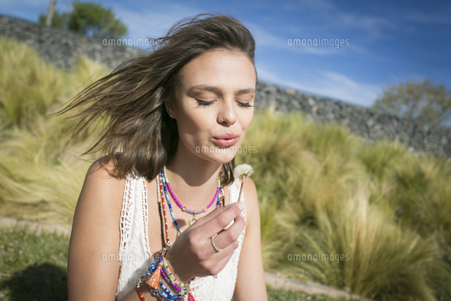 Caucasian woman on hill blowing on dandelion