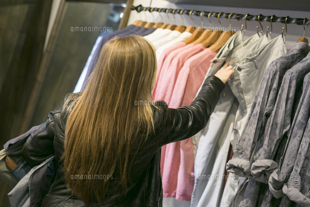 Caucasian woman examining jeans in clothing store