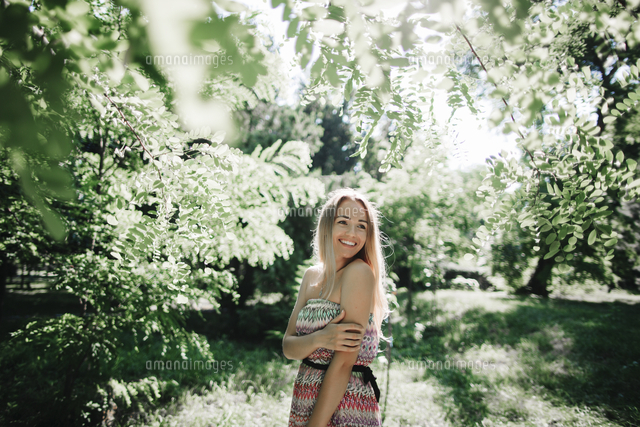 Caucasian woman standing near green trees
