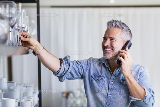 Caucasian man reaching for glassware talking on telephone