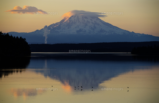 Reflection of clouds and mountain in river at sunset