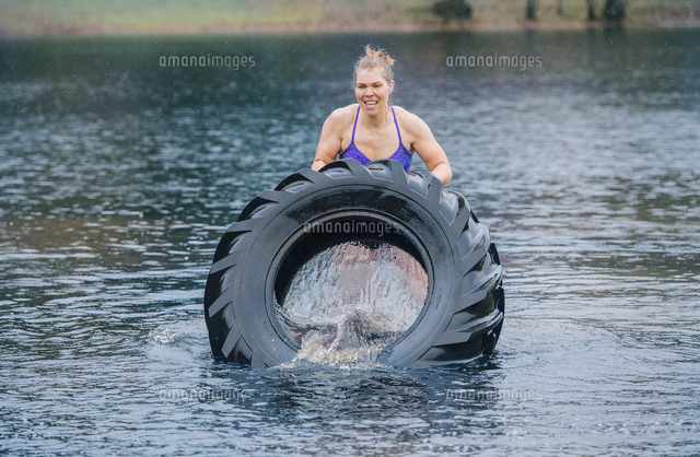 Caucasian woman pushing heavy tire in lake
