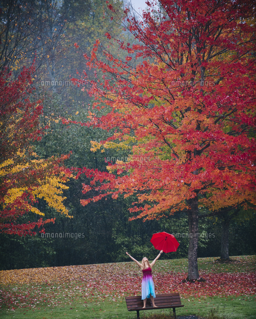 Caucasian woman holding umbrella in rain on park bench