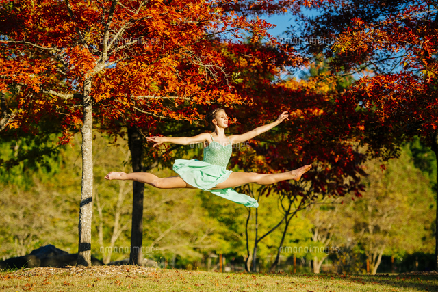 Caucasian ballerina leaping under branches in park