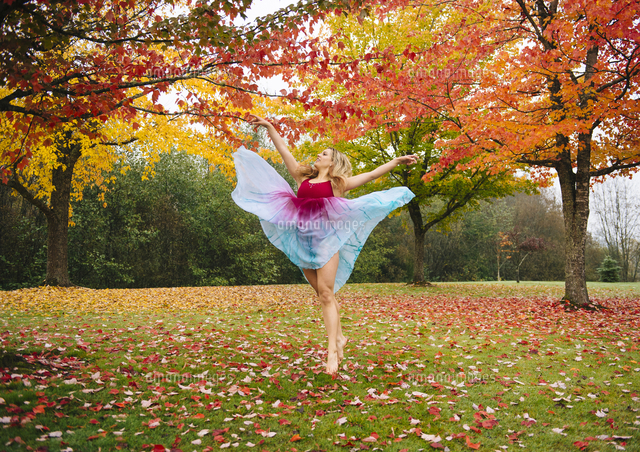 Caucasian ballerina dancing in autumn leaves in park