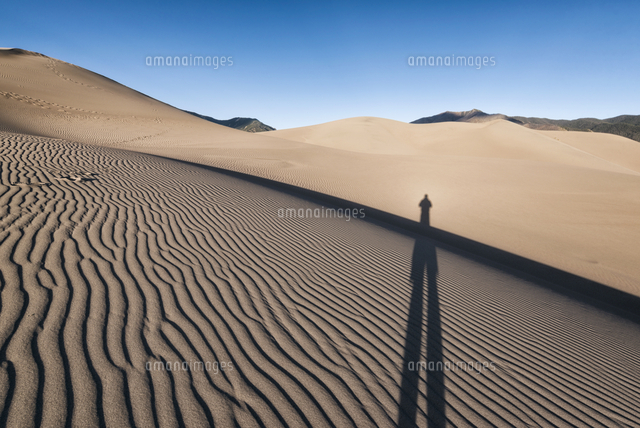 Shadow of person on sand dunes