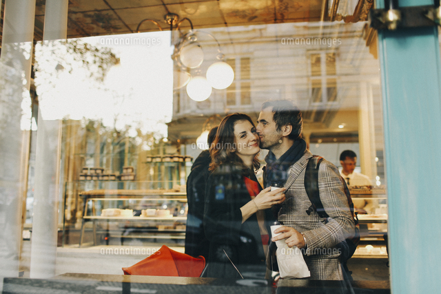 Caucasian man kissing woman on cheek behind bakery window