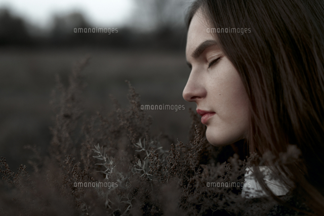 Caucasian woman smelling foliage