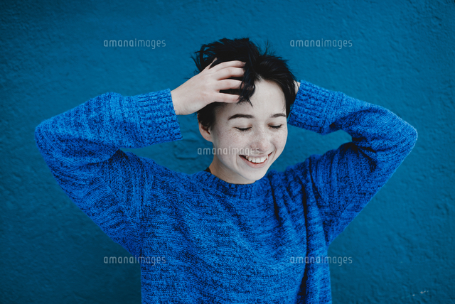 Smiling Caucasian woman tousling hair near blue wall