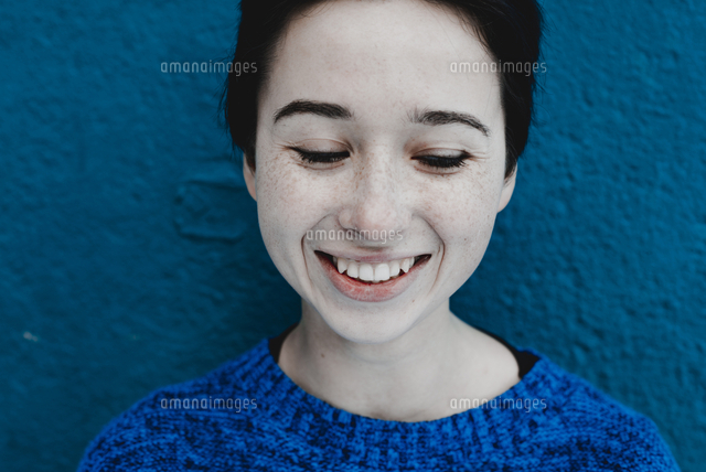Smiling Caucasian woman near blue wall