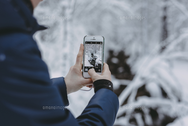 Caucasian woman photographing snow with cell phone