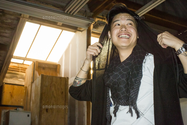 Androgynous Asian man holding scarf on head
