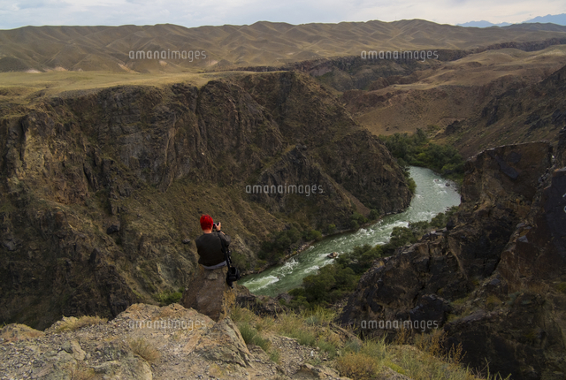 Caucasian woman sitting on mountain rocks photographing river