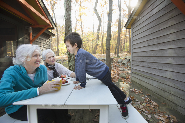 Grandmothers enjoying breakfast outdoors near cabin with grandson