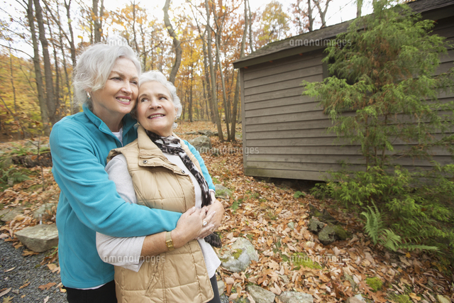 Caucasian women hugging outdoors near cabin