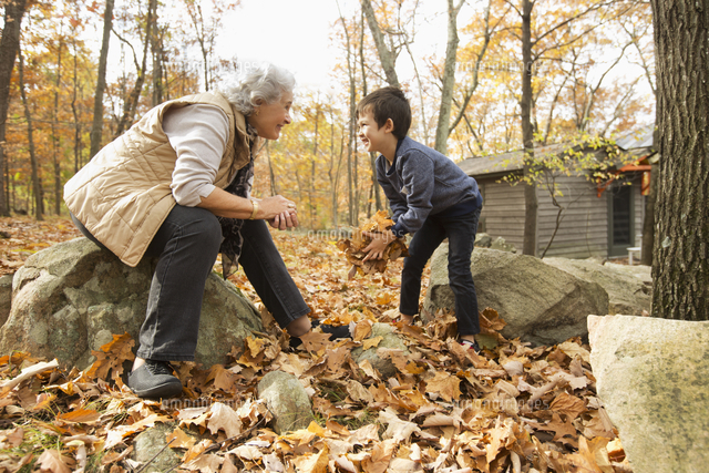 Grandmother and grandson playing with autumn leaves