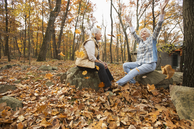 Caucasian women playing with autumn leaves