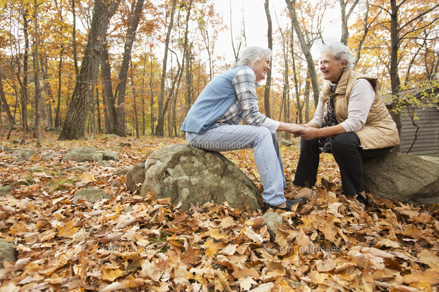 Caucasian women holding hands outdoors in autumn