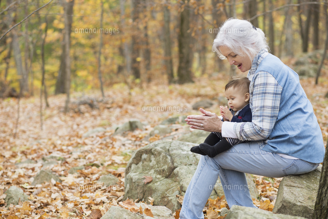 Grandmother playing with baby grandson in autumn