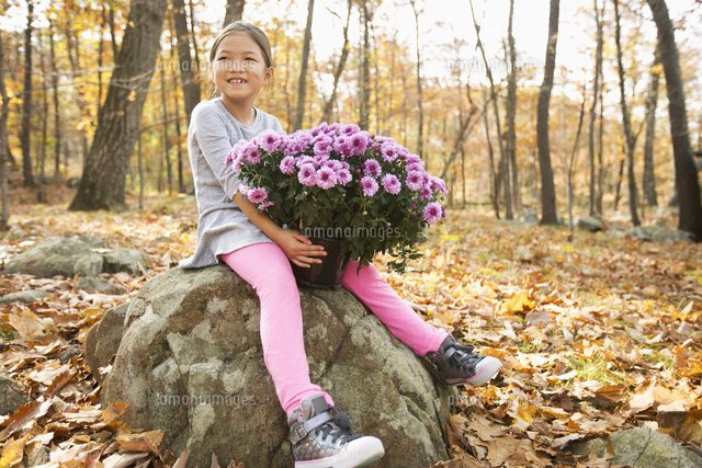 Smiling Mixed Race girls sitting on rock in autumn holding flowers