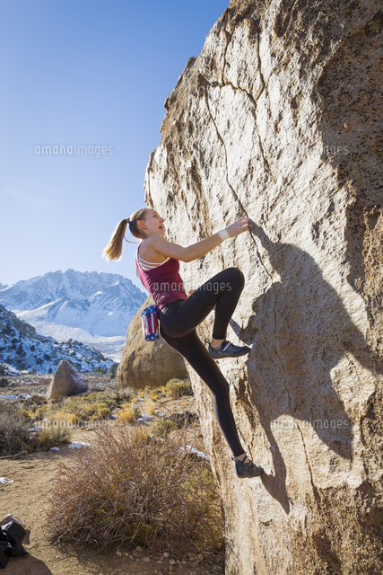 Caucasian teenage girl climbing rock