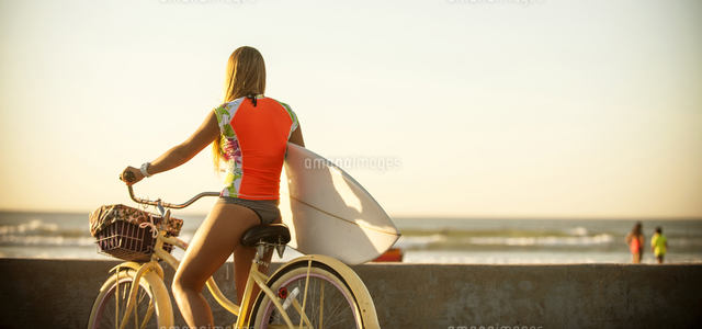 Caucasian teenage girl carrying surfboard on bicycle