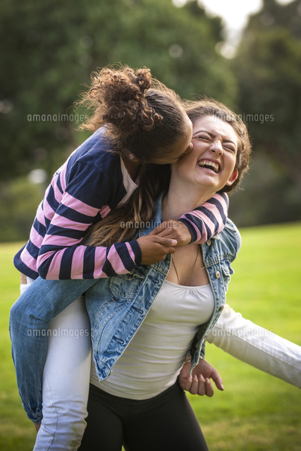 Portrait of laughing girl carrying sister piggyback
